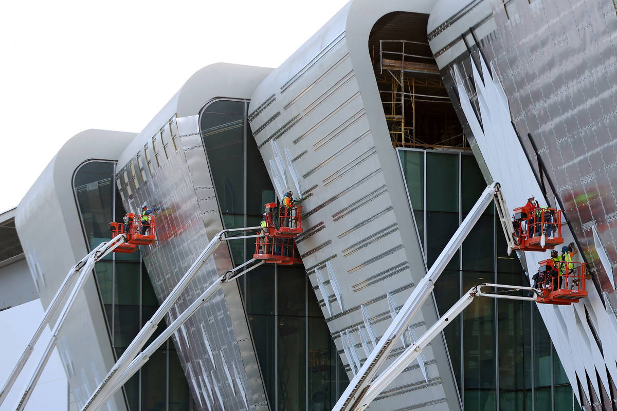 Workers finish the exterior walls on the west side of the Las Vegas Convention Center expansion ...