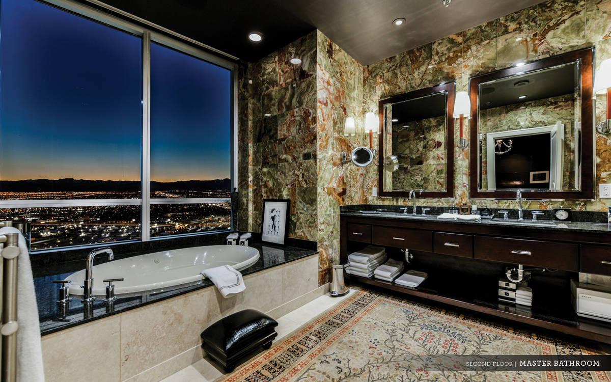 The spa-like master bath showcases multicolored granite-esque stone walls, soaking tub with a v ...