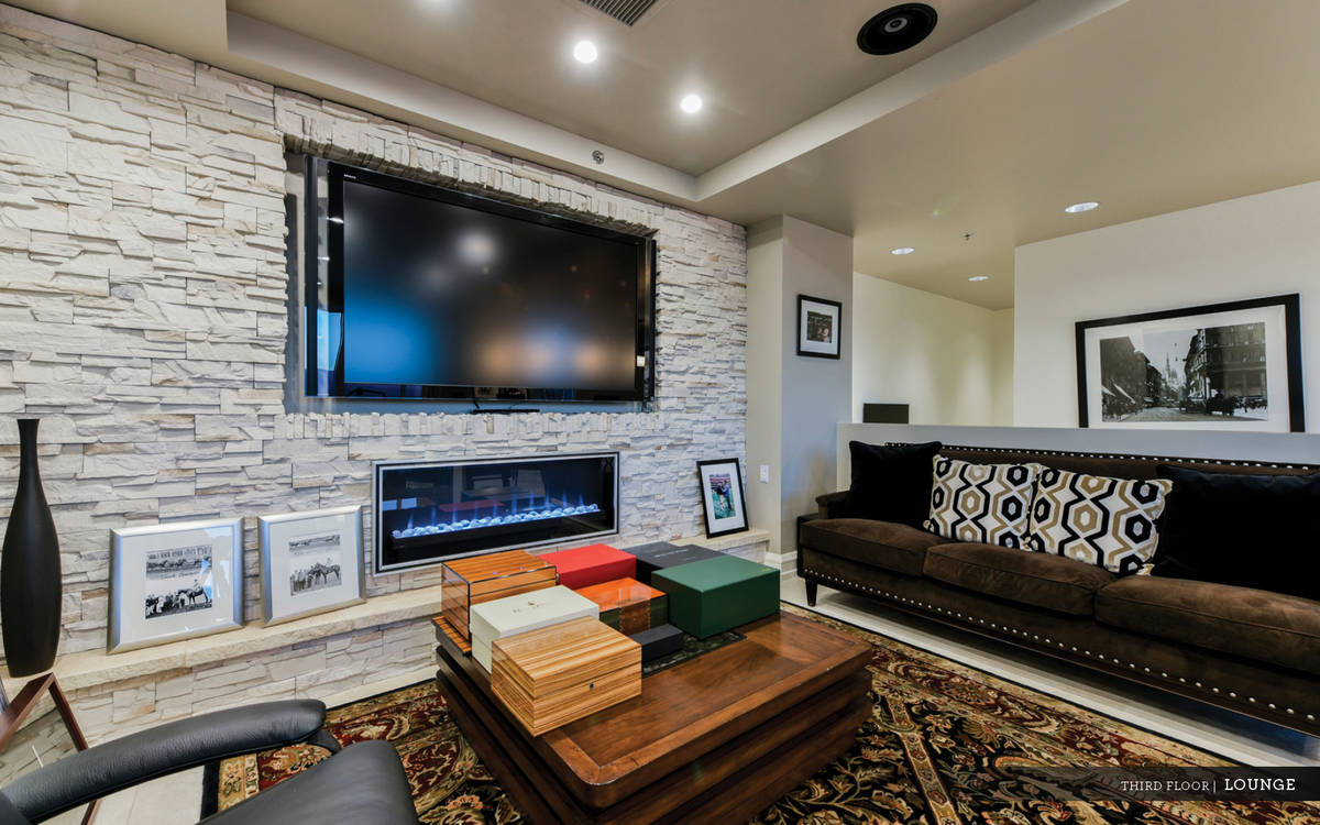 The third level is designed as a lounge area with a stacked stone linear fireplace, wet bar, ba ...