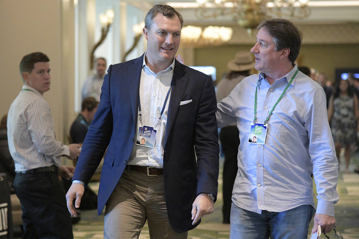 San Francisco 49ers general manager John Lynch chats with Don Banks, right, while walking to a ...