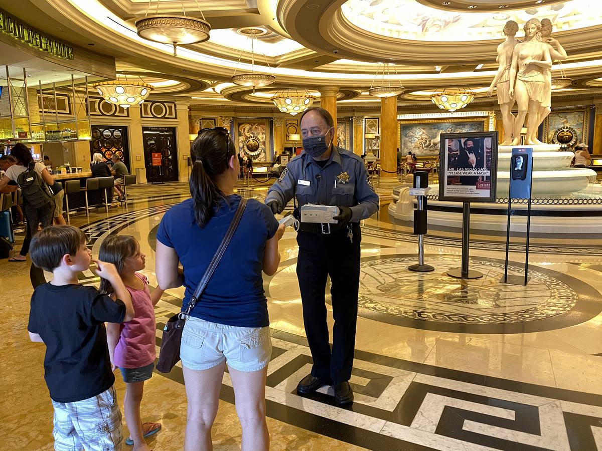 A security guard hands out face masks at Caesars on the Strip in Las Vegas Wednesday, June 24, ...