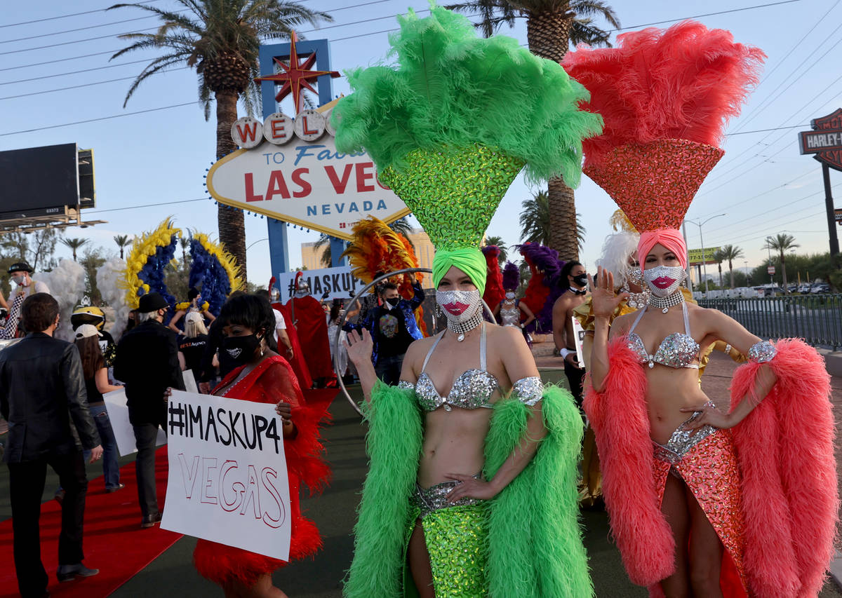 Showgirls and entertainers pose at the Welcome to Fabulous Las Vegas sign on the south Strip in ...