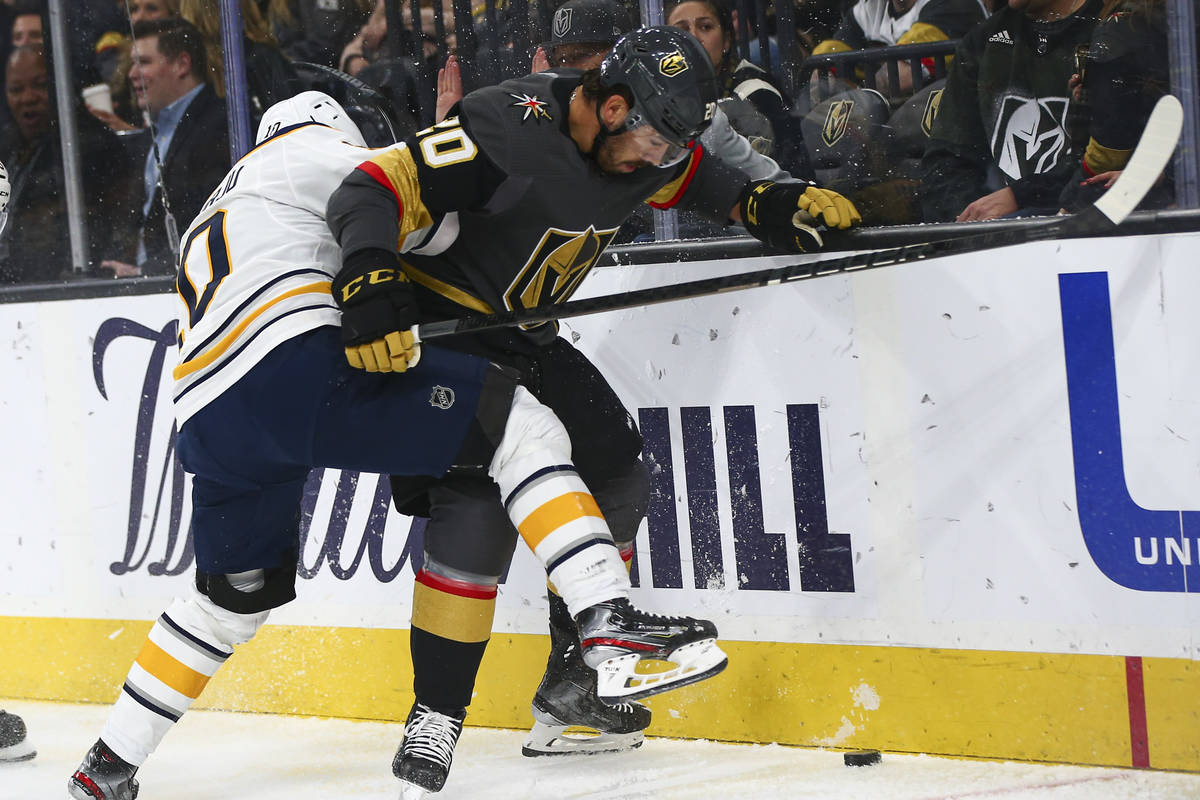 Buffalo Sabres' Henri Jokiharju (10) battles for the puck against Golden Knights' Chandler Step ...