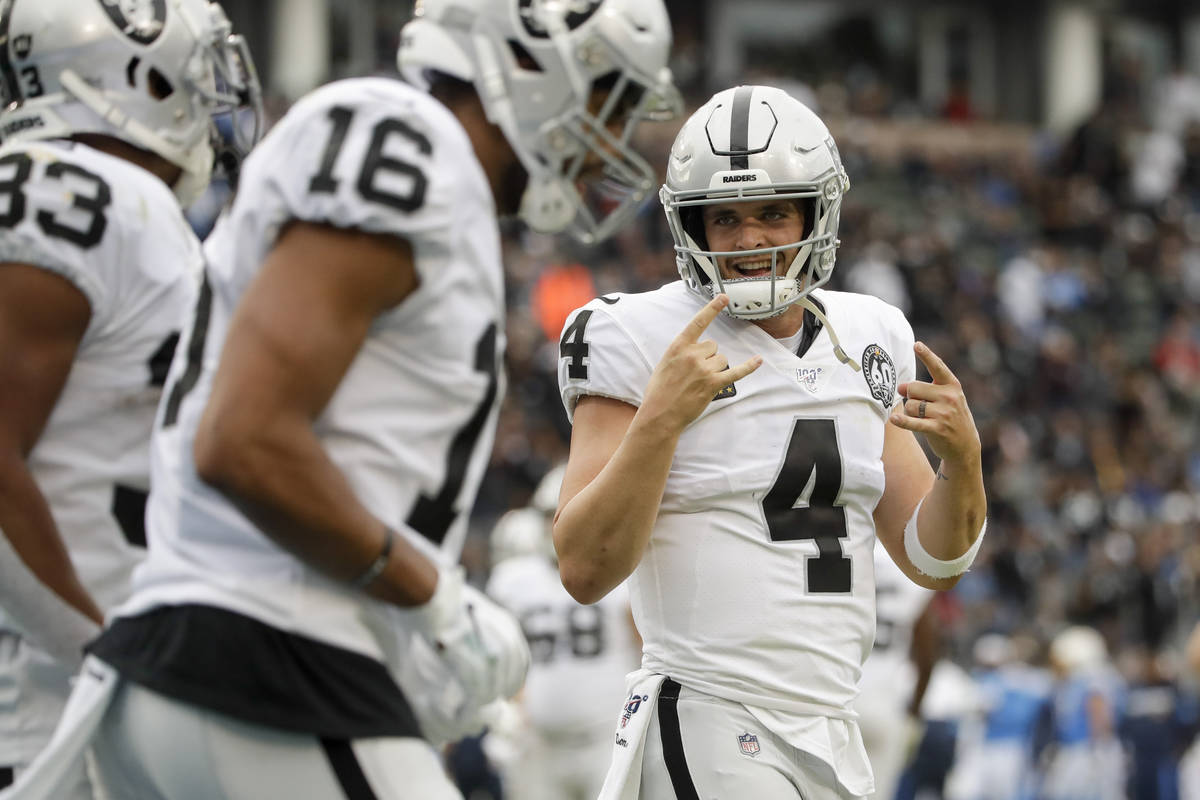 Oakland Raiders quarterback Derek Carr celebrates after a touchdown by running back DeAndre Was ...