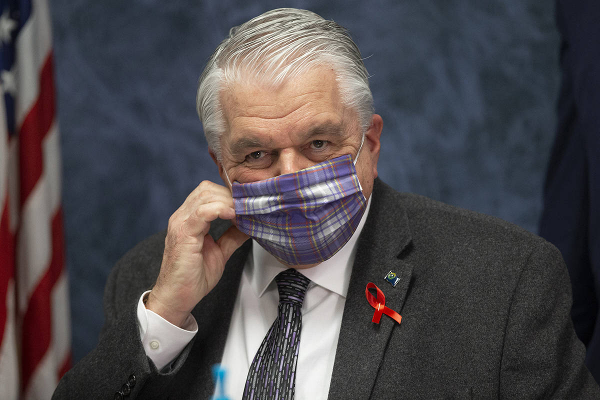 Gov. Steve Sisolak wears a protective mask before the start of a press conference to update Nev ...