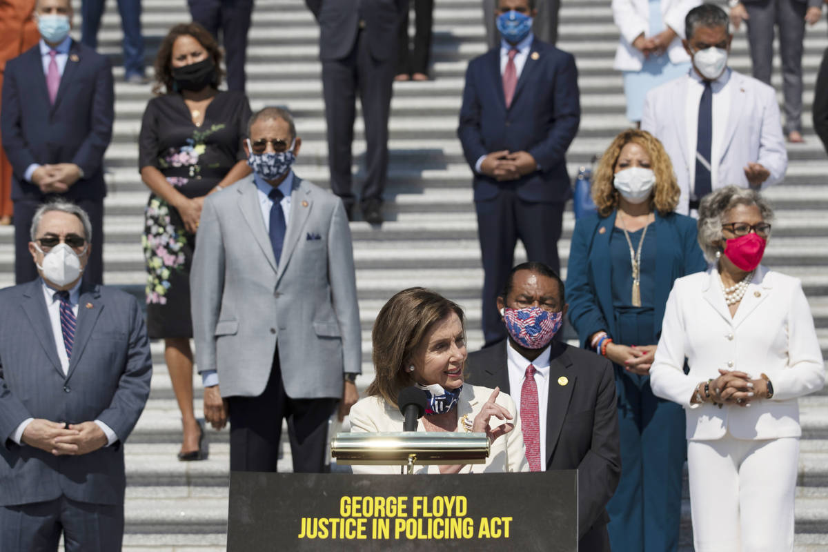 House Speaker Nancy Pelosi of Calif., joined by House Democrats spaced for social distancing, s ...