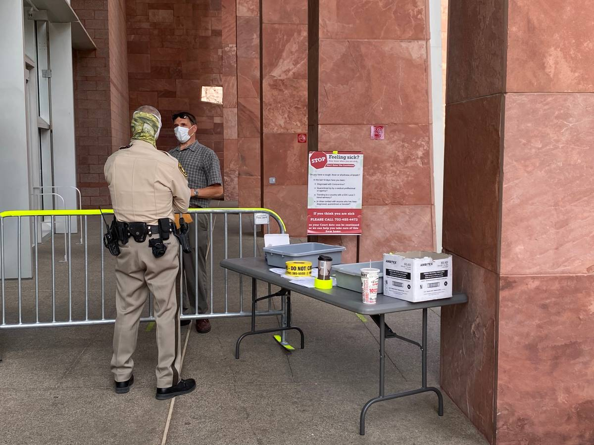 Masked marshals guarded the entrance to the Regional Justice Center, where a mask order has bee ...