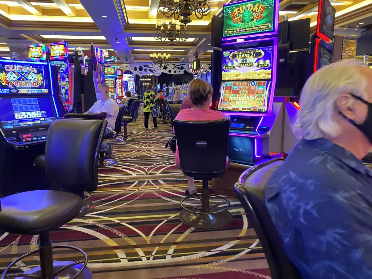 Slot players at Green Valley Ranch casino on Friday were largely adhering to a new state mandat ...