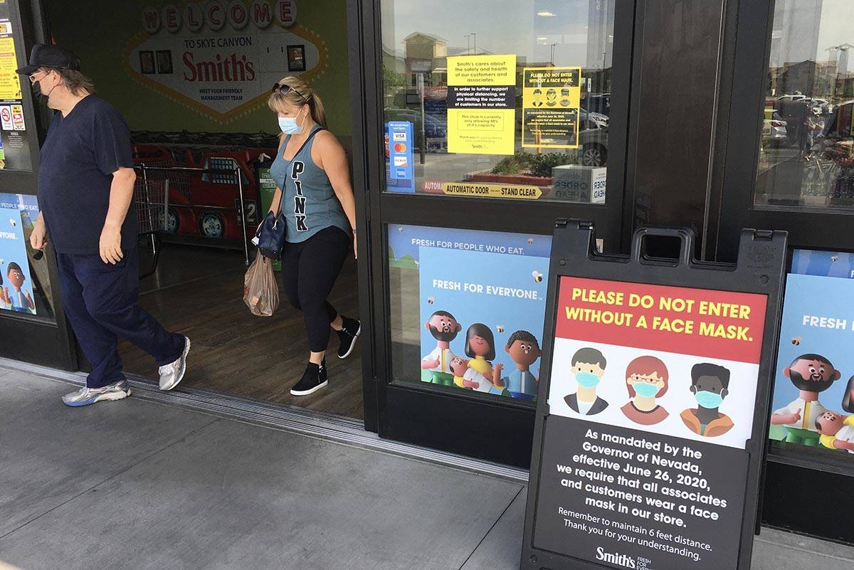 A sign informs people to wear a mask before entering the Smith's Marketplace on Skye Canyon P ...