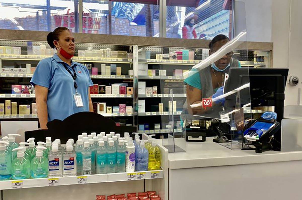 Clerks at Walgreens at Fremont and 4th streets wear face masks below their chins on Friday, Jun ...