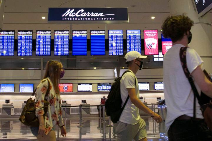 Arriving passengers walk past McCarran International Airport sign on Wednesday, June 24, 2020, ...