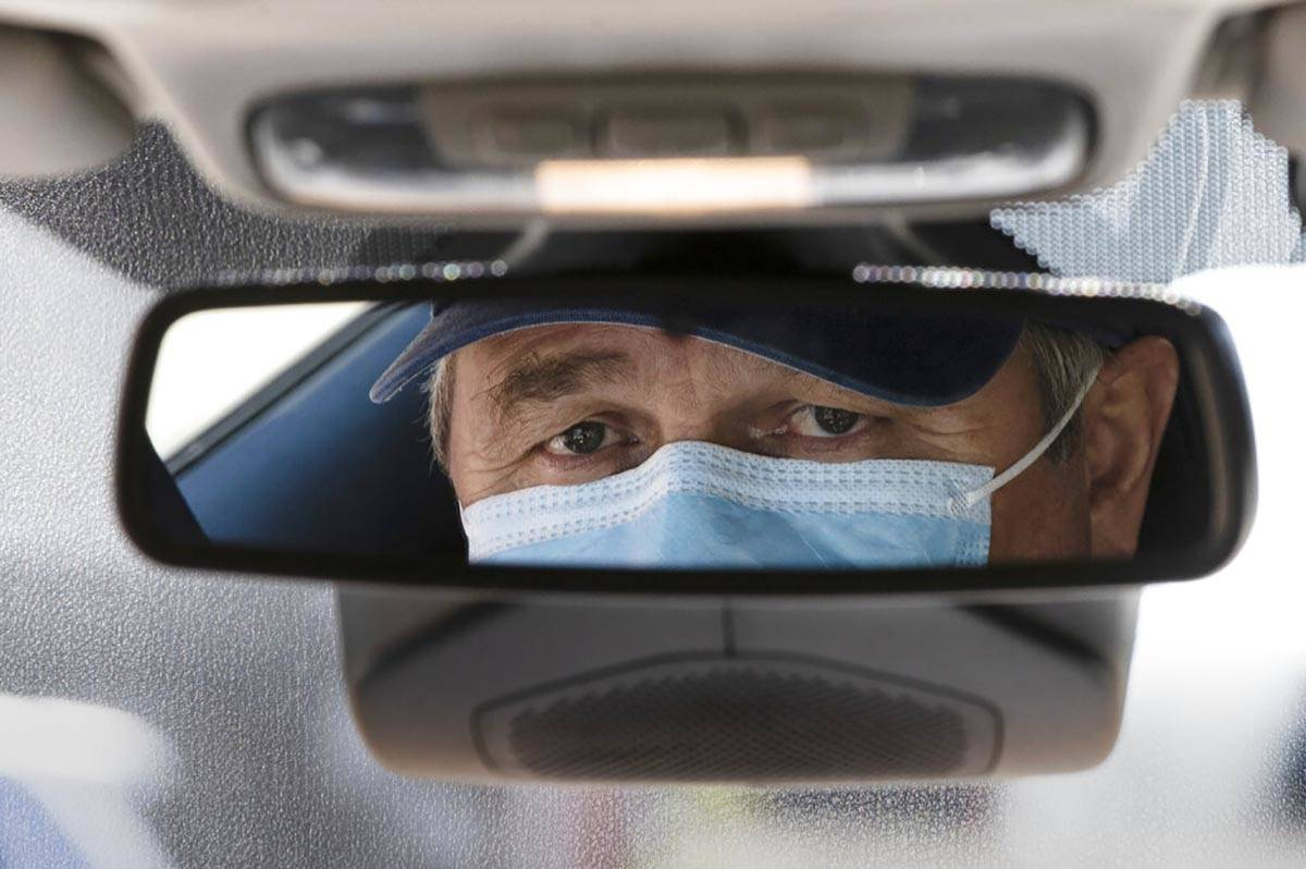 Taxi driver Nicolae Hent, wearing a protective mask, poses for a photograph before before start ...