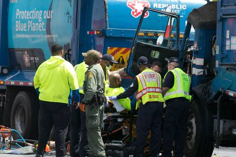 Emergency medical service workers remove a driver from his truck after a crash involving two ga ...