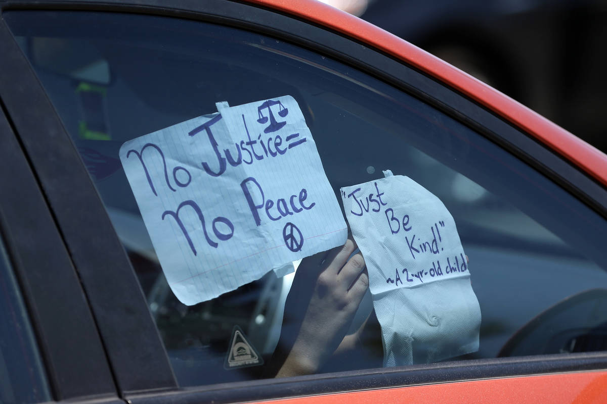 A person hangs a sign inside their car in advance of a Black Lives Matter parade from the Clark ...