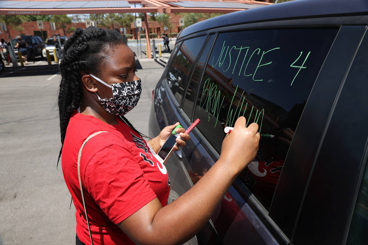 Tia Coward, event organizer and Las Vegas resident, writes a message on her car in advance of a ...