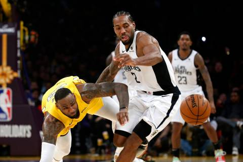 Los Angeles Lakers' LeBron James, left, and Los Angeles Clippers' Kawhi Leonard (2) chase the b ...