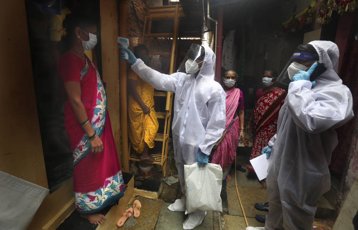A health worker checks the body temperature of a resident, as others await their turn during a ...