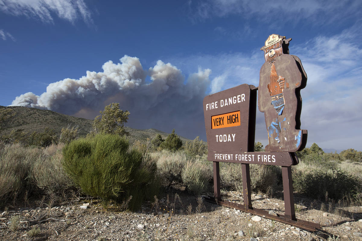 A Smokey the Bear sign indicates very high fire danger as the plume of smoke from the Mahogany ...