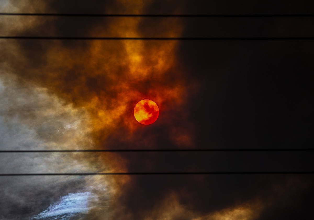 The sun is blanketed in red smoke originating from a wildfire at Mount Charleston on Sunday, Ju ...