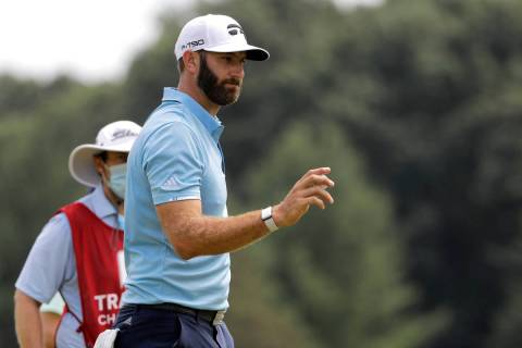 Dustin Johnson acknowledges people on the homes along the fifth green after putting during the ...