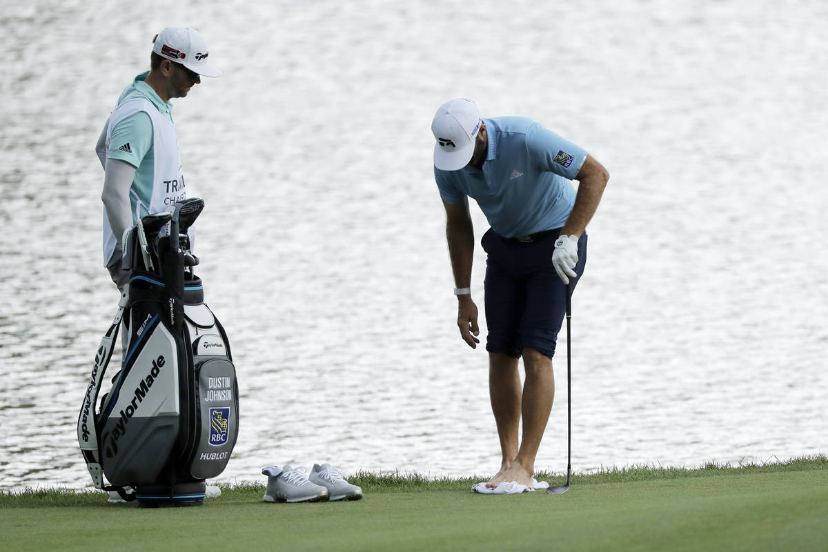 Dustin Johnson, right, cleans his feet after having to go in the pond to hit a ball on the roug ...