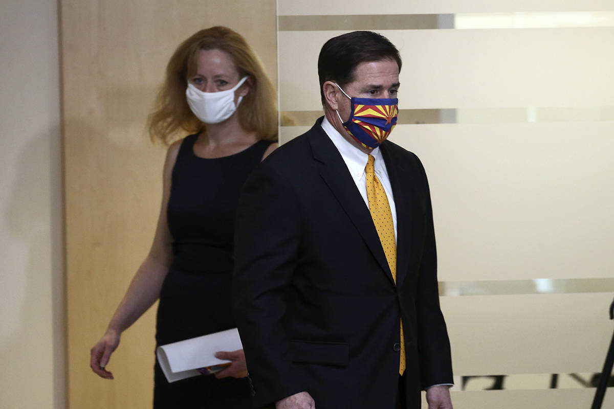 Arizona Republican Gov. Doug Ducey, right, and Arizona Department of Health Services Director D ...