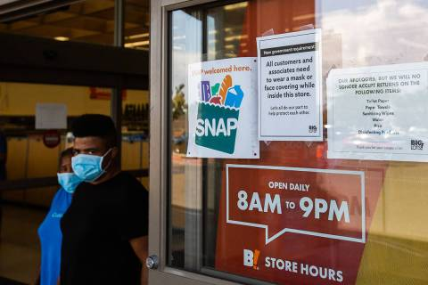 Customers wearing masks leave Big Lots next a sign stating that masks are required to enter in ...