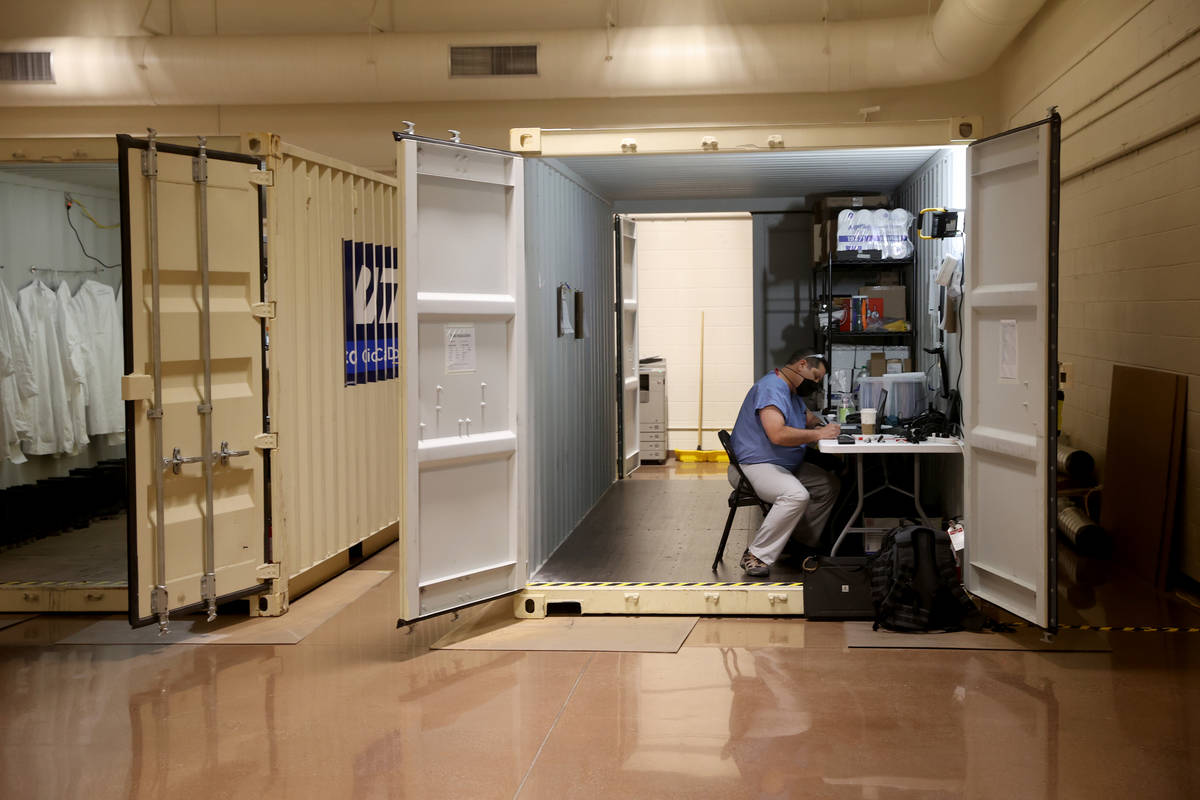A worker in an administrative container at the Battelle Critical Care Decontamination System si ...
