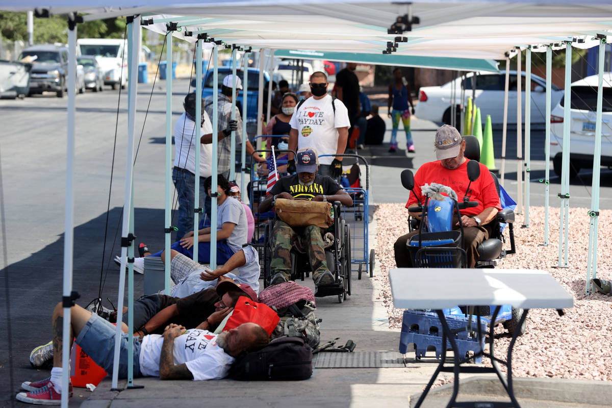 People line up for a food distribution at SHARE Village, formerly known as Veterans Village, in ...