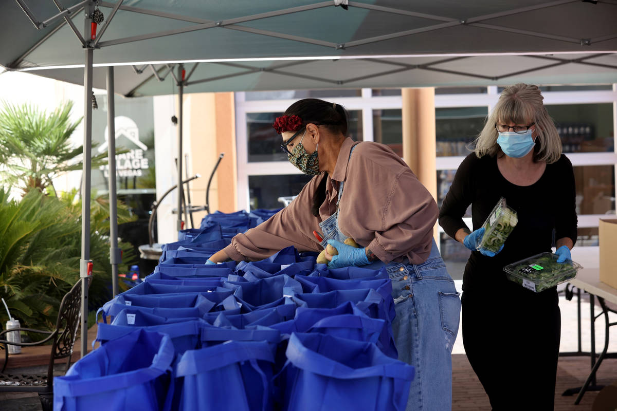 Volunteers Carrie Smith, left, and Shannon Oleson prepare bags for a food distribution at SHARE ...