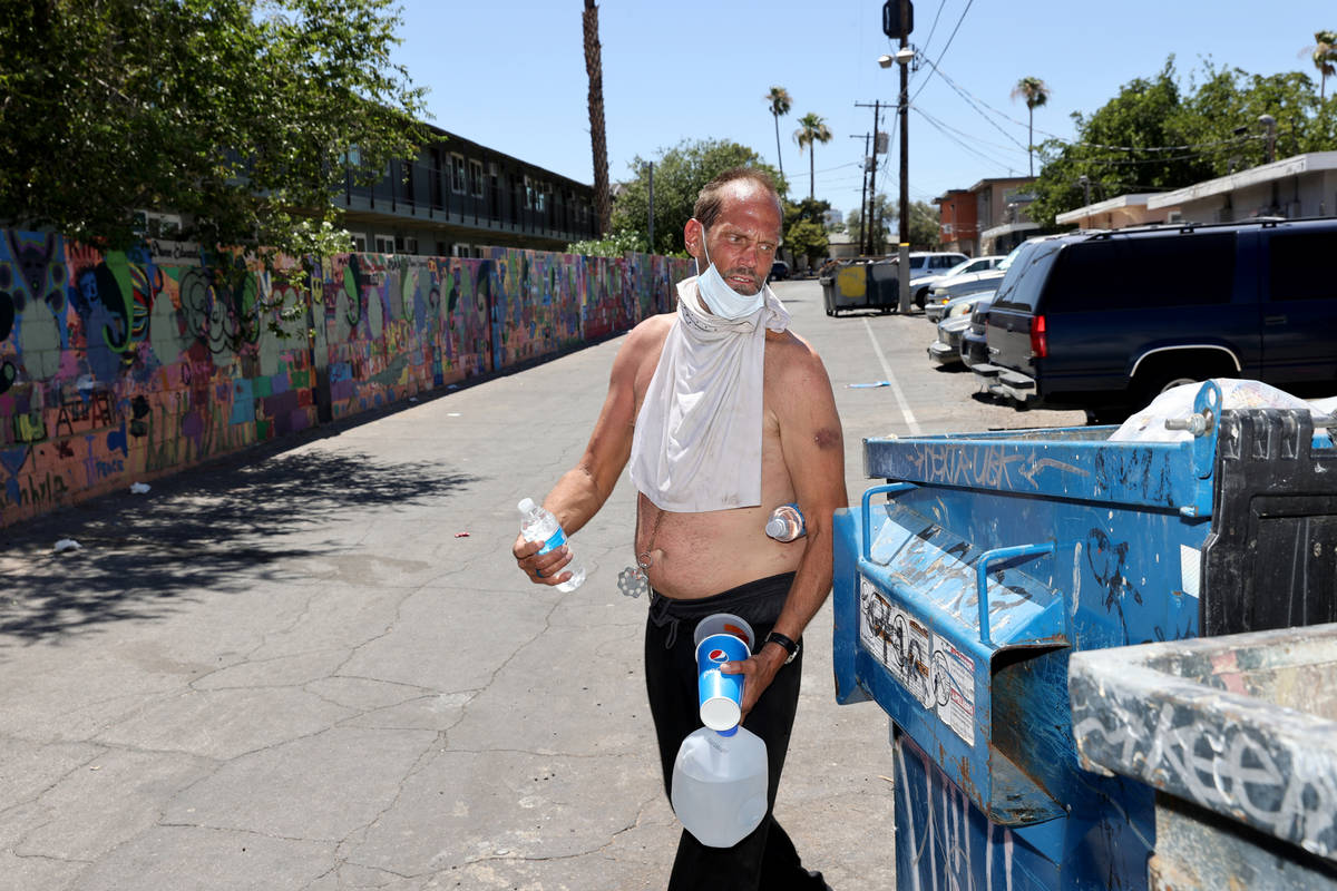 Eric Michael Wynn, 53, walks back to his camp after getting water in the front office at SHARE ...