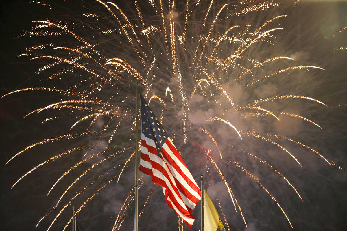 FILE - In this July 4, 2015, file photo, fireworks explode behind a United States flag during a ...