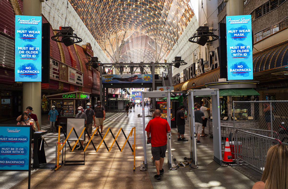 People walk through temperature scanners at the Fremont Street Experience in downtown Las Vegas ...