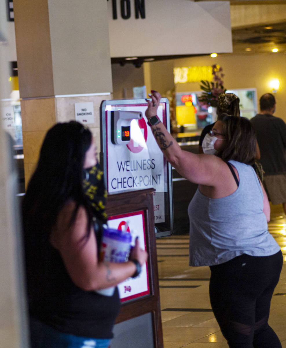 A woman holds up her wrist for a temperature check at the Golden Gate in downtown Las Vegas on ...