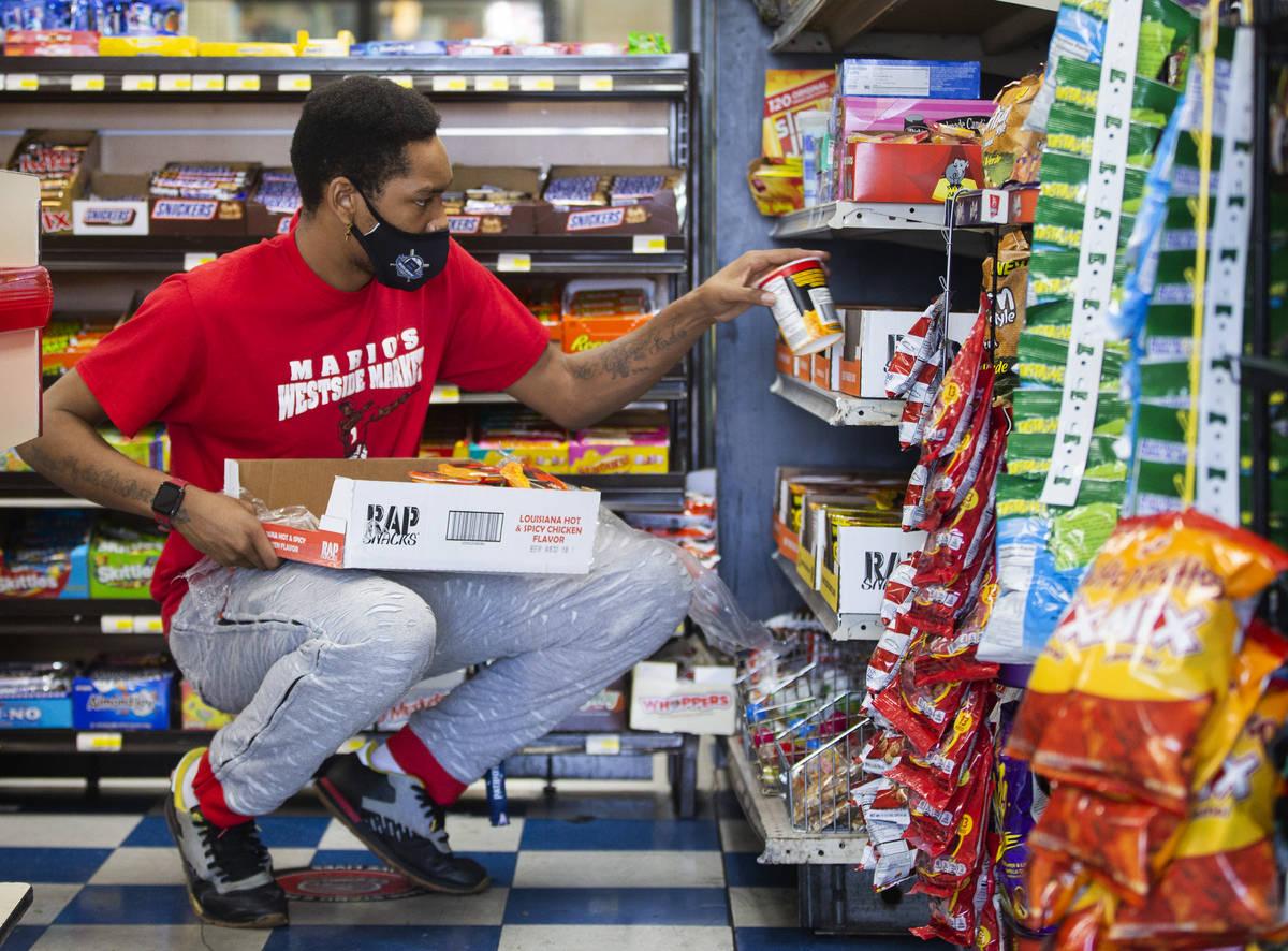Deshaun Lewis, unofficially adopted son of Mario Berlanga, stocks shelves at Mario's Westside M ...