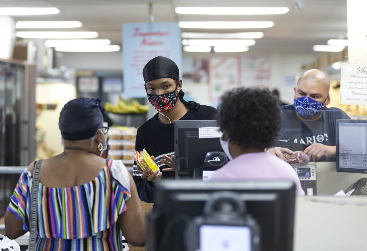 Cashier Marqeuiz Walls, left, and Juan Cisneros check out customers at Mario's Westside Market ...