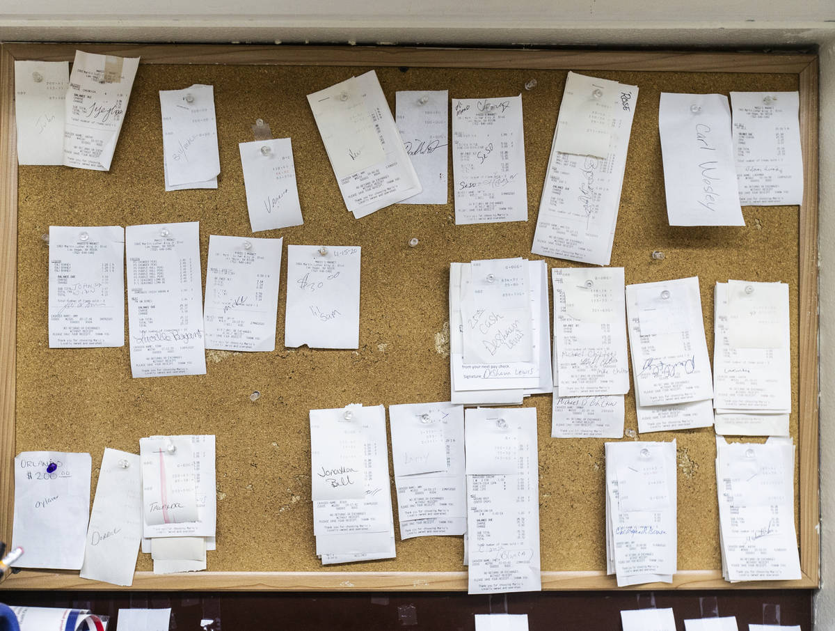 A bulletin board showing customer receipts that owner Mario Berlanga has forgiven, with the pro ...