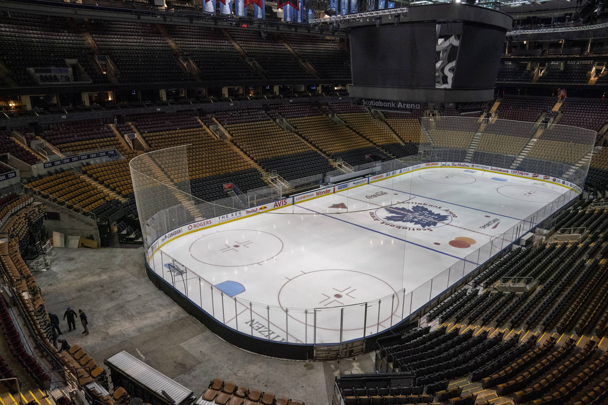 Workers stand by after pausing the assembly of the arena for the Maple Leafs NHL hockey game ag ...
