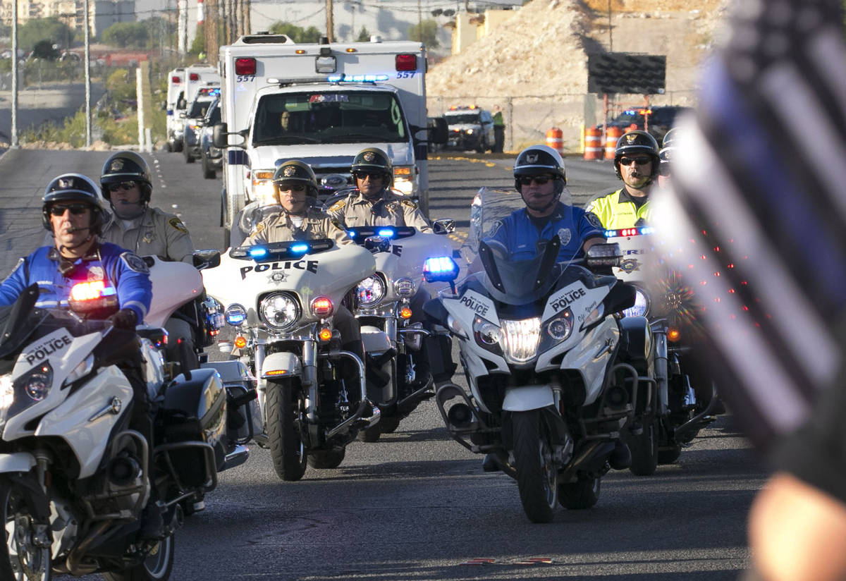 An ambulance carrying a wounded Las Vegas police officer Shay Mikalonis is seen during a proces ...