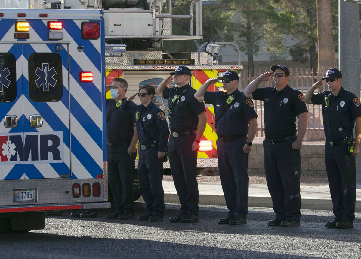 Clark County Firefighters salut during a procession as an ambulance carrying a wounded Las Vega ...