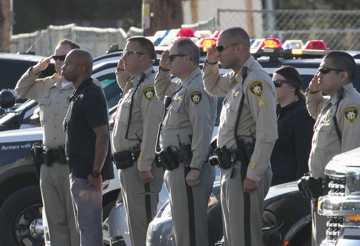 Las Vegas police officers salut during a procession as an ambulance carrying a wounded Las Vega ...