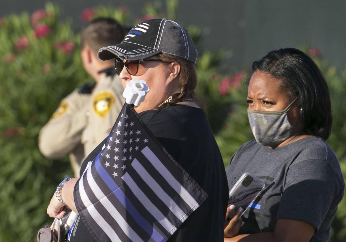 Cindy Novak, left, and Nakia Jackson-Hale watch a procession as an ambulance carrying a wounded ...