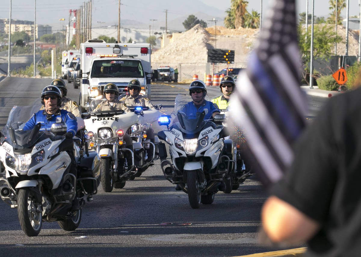 Cindy Novak, right, watches a procession as an ambulance carrying a wounded Las Vegas police of ...