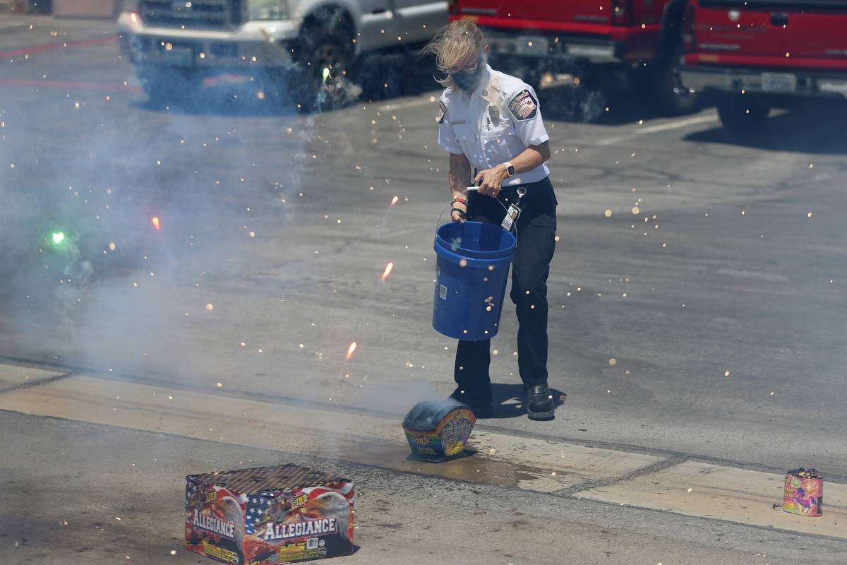 Las Vegas Fire and Rescue's fire inspector Melanie Dennon pours water on a box of fireworks dur ...