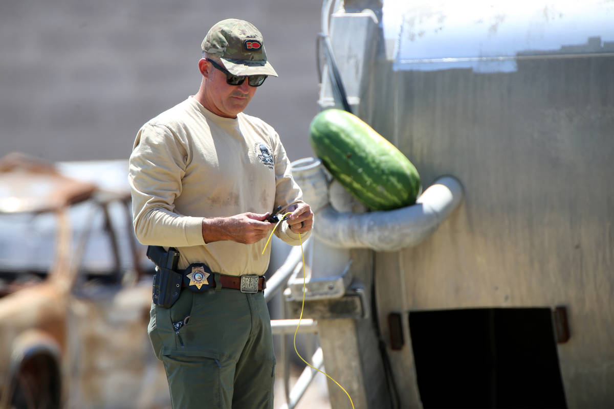 Mark Duncan, bomb squad technician with Las Vegas Fire and Rescue, sets up a charge to blow up ...