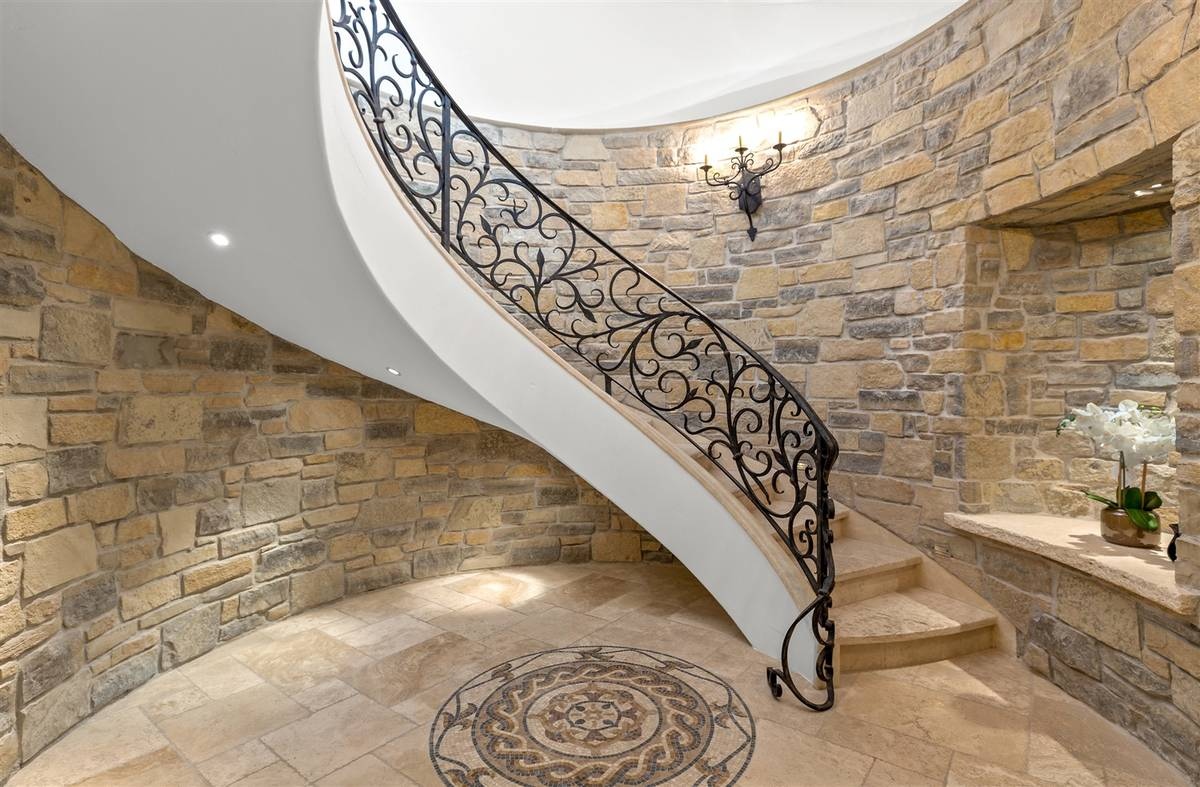 The grand staircase leads to the entertainment level downstairs. (Luxurious Real Estate)
