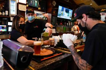 Jessica Ciaramitaro, Daryn Feenstra and Nicholas Soriano mix drinks while wearing face masks at ...