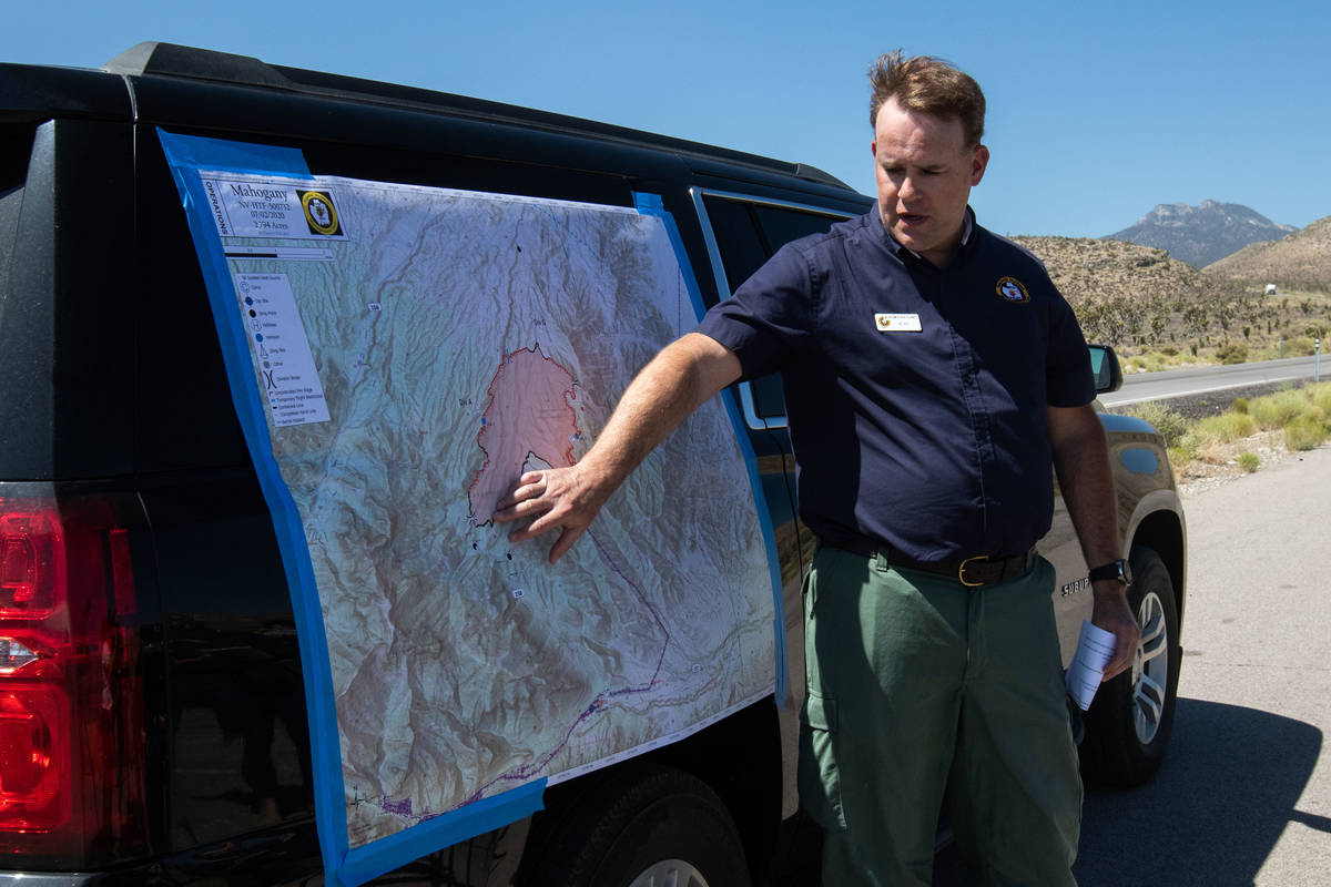 Jeremy Kiesling, the incident commander trainee with Great Basin Team 7, indicates on a map an ...