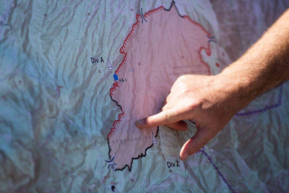 Jeremy Kiesling, the incident commander trainee with Great Basin Team 7, points to a map of the ...