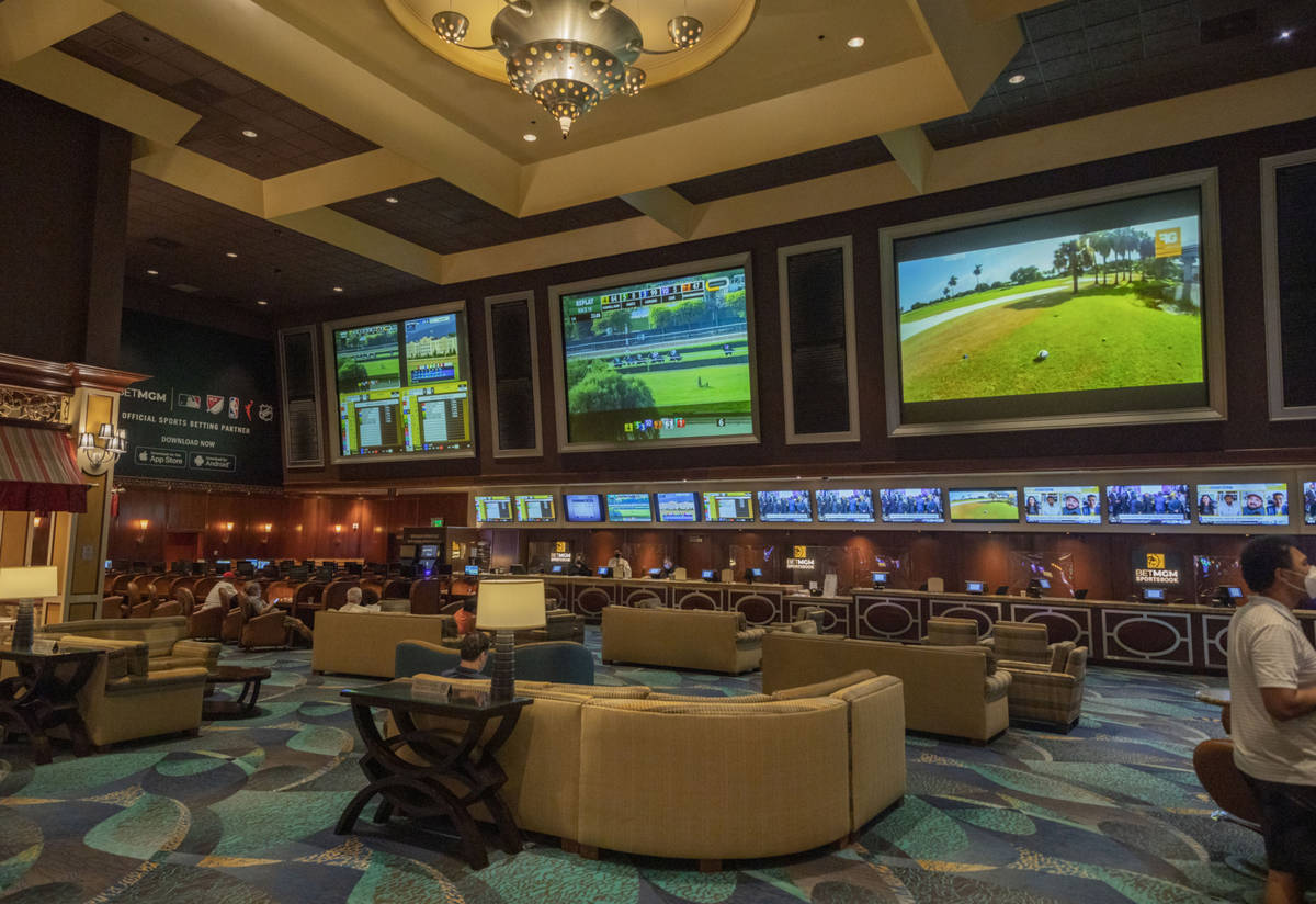 Individuals wait for a horse race to begin on the reopening of the Bellagio sportsbook, Thursda ...
